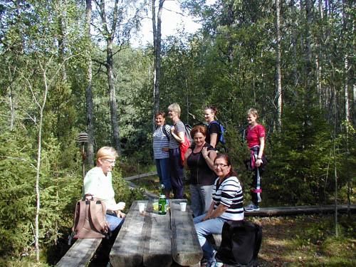 Ihmisiä juttelemassa pöydän ääressä metsässä.